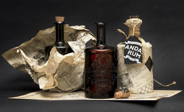 """Các chai rượu rum được bao bọc trong bản sao của """"Mandalay Gazette"""", một tờ báo thuộc địa, viết về câu chuyện của Mandalay Rum"""